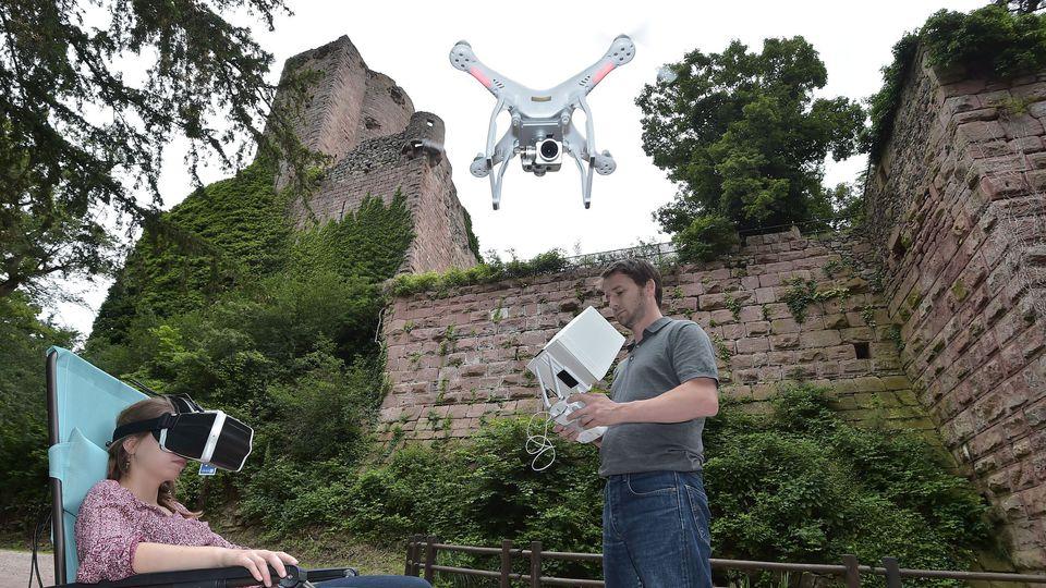 Une femme porte un casque vidéo sur les yeux et visite le château de Kintzheim grâce à la diffusion d'images haute définition tournées par un drone, le 21 juin 2016 afp.com/PATRICK HERTZOG